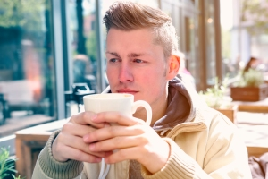 young man sitting outside and drinking coffee